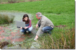 man and woman testing water and tracking data on a laptop