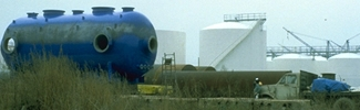 A large blue aboveground storage tank on a grassy field at an industrial facility