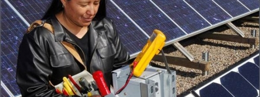 Woman with electric multi-tester working on solar panels