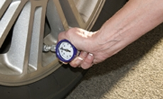 photo of man checking tire pressure