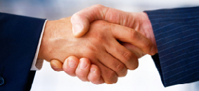 Two disjointed hands, coming out of different suit sleeves, in a handshake