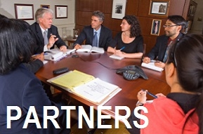 Photo for 'Partners': A group of people wearing suits talking around a wooden conference table