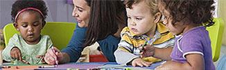 Picture of three toddlers sitting with a woman at a table playing with crayons.