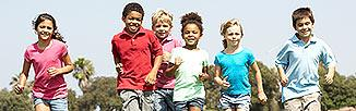 Picture of small children running outside on a bright sunning day.