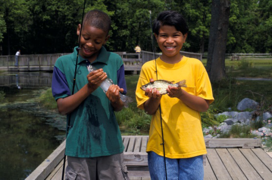 Two boys holding small fish that they caught