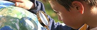 Image of a young student looking at a globe
