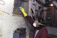 Person cleaning mold while wearing protective equipment