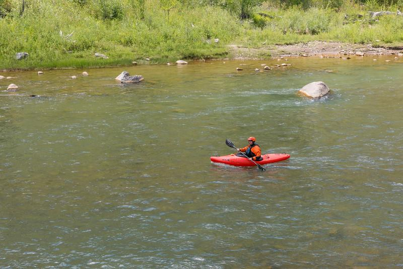 a person in a red kayak on a wilderness river