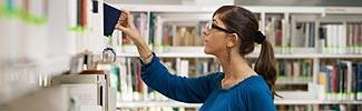 Woman looking at library shelf searching for additional information