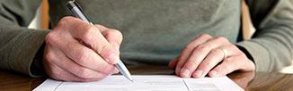 image of a person's hand holding a pen filling out a form