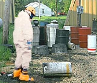 Man in hazmat suit looking at a canister