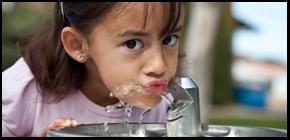 Closeup of girl drinking from water fountain.