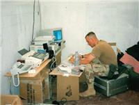 Sgt. Danny Hart, U.S. Army, 55th Signal Company (combat camera), hard at work in Mogadishu at his desk constructed of MRE boxes.