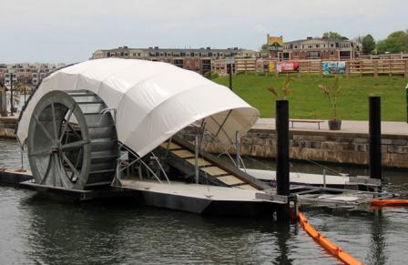 Water wheel on side drives a conveyer belt that pulls floating trash from a portion of the harbor. Boom direct trash to mouth of the conveyer belt. Looks rather like a snail, with conestoga wagon like cover.