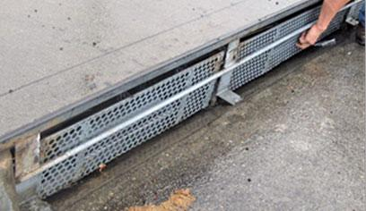Automatic curb inlet cover: curbside water inlet with metal plate that has one inch holes for water to pass through. The metal plate has a horizontal bar running through the center that pivots the screen to close when trash pushes up against the grate.