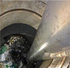 View down a Hydrodynamic Separator: cylindrical concrete catchment with trash at the bottom.