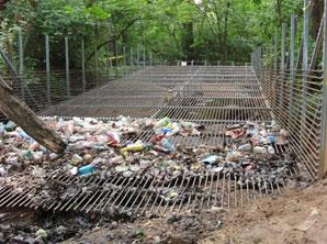 Large, metal cage-like structure with cage on bottom and two sides crossing a river and filled with trash