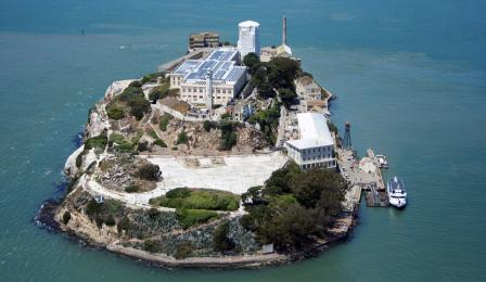 Aerial view of Alcatraz with solar panels on roof of main building clearyl visible, covering entire roof.